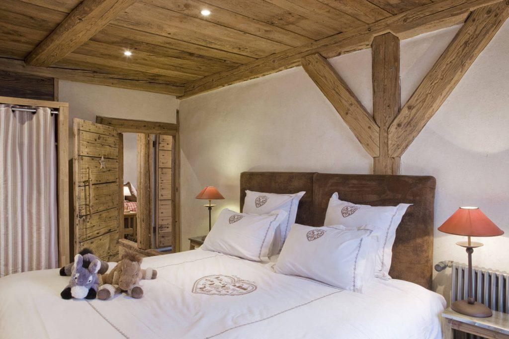 Chambre avec lit blanc dans un chalet rustique