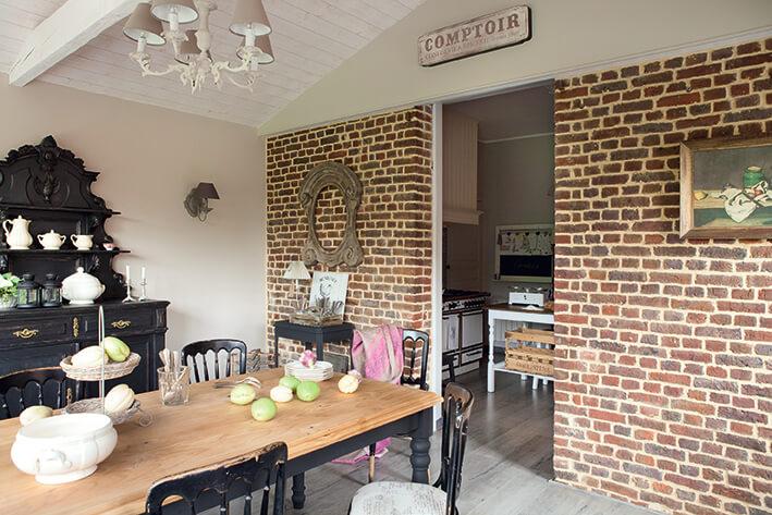 Salle à manger avec table en bois et mur de brique dans une maison classique chic