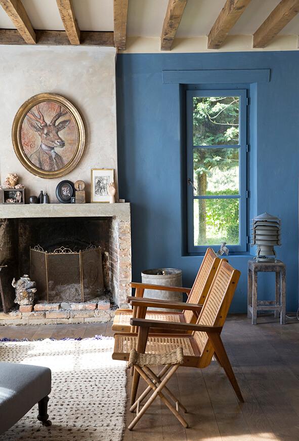 Salon avec chaise et mur bleu dans maison authentique