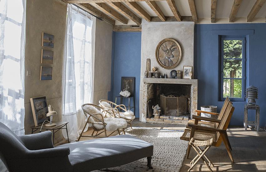 Salon avec mur bleu, canapé et chaises dans une maison de normandie