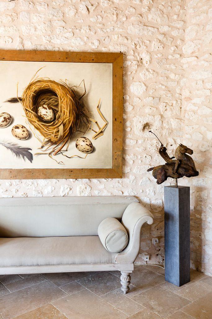 Salon avec une peinture sur le mur d'une maison de campagne à l'intérieur rustique chic