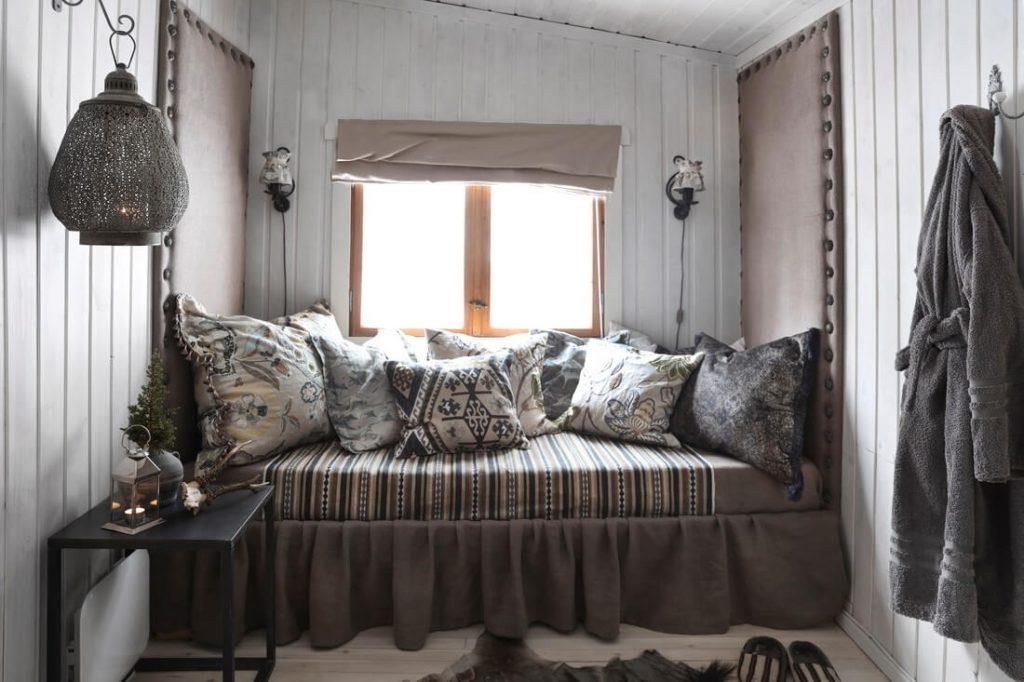canapé avec coussins dans chalet cosy à la déco bohème chic