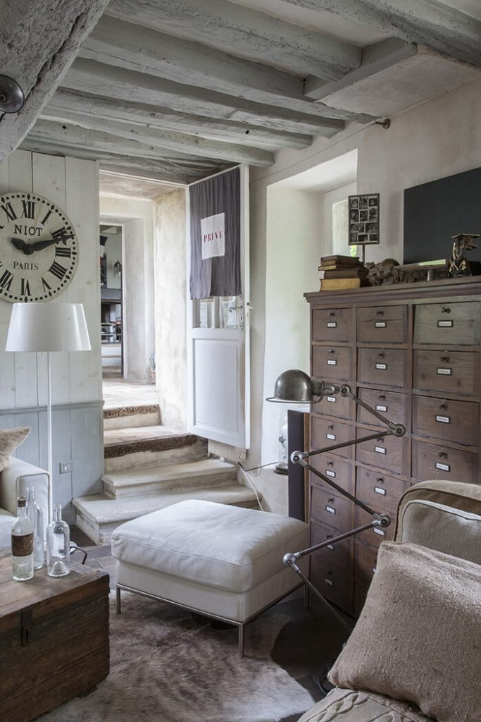Chambre avec meuble en bois et lampe dans une maison de campagne à la déco récup chic