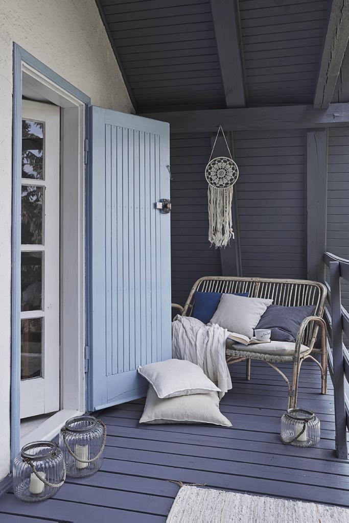Terrasse avec porte bleue et coussins maison de campagne à la décoration style romantique