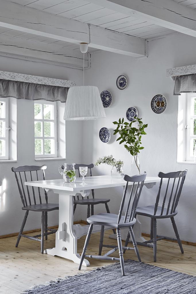 Cuisine avec table blanche et chaises grises dans une maison de campagne à la décoration style romantique chic