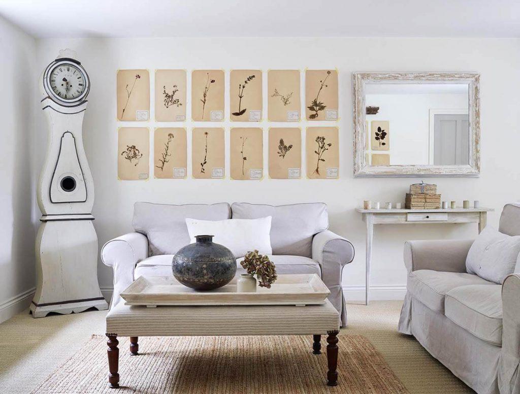Salon avec canapé et coussins dans une maison de campagne à la décoration romantique chic à Sussex