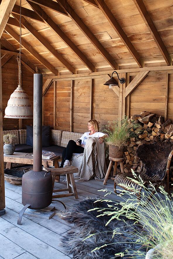 Propriétaire d'une maison de campagne au style épuré assise sur un canapé de sa terrasse