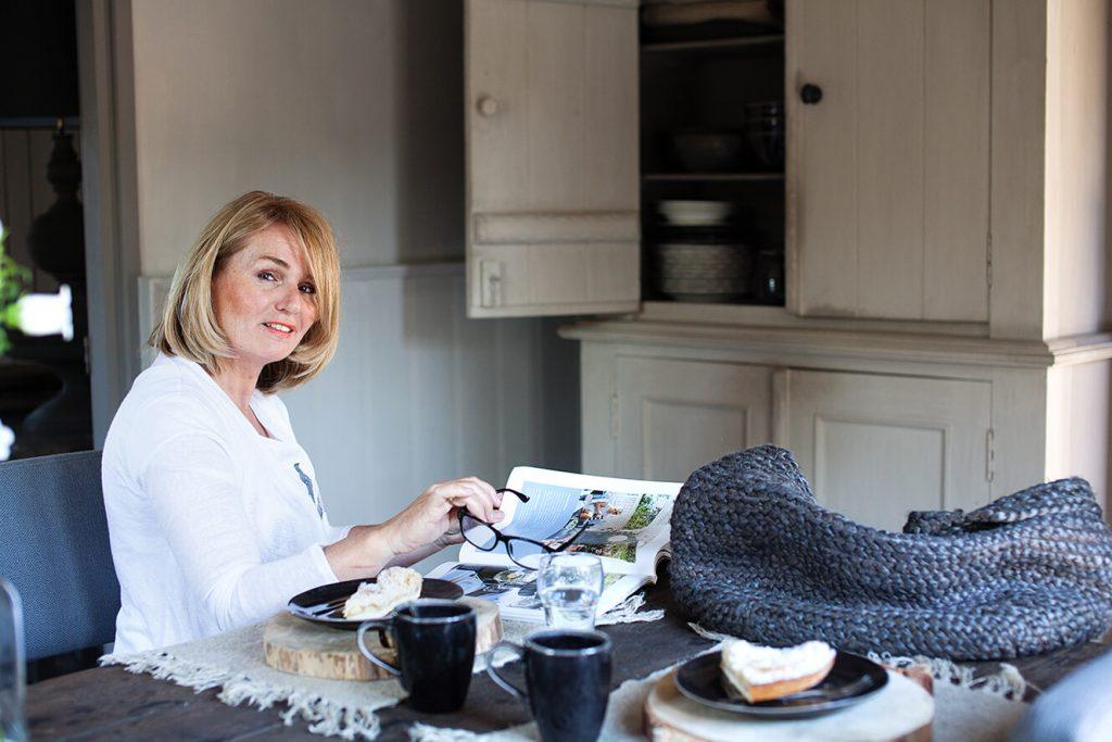 Propriétaire d'une maison de campagne assis sur une chaise de sa cuisine au style épuré