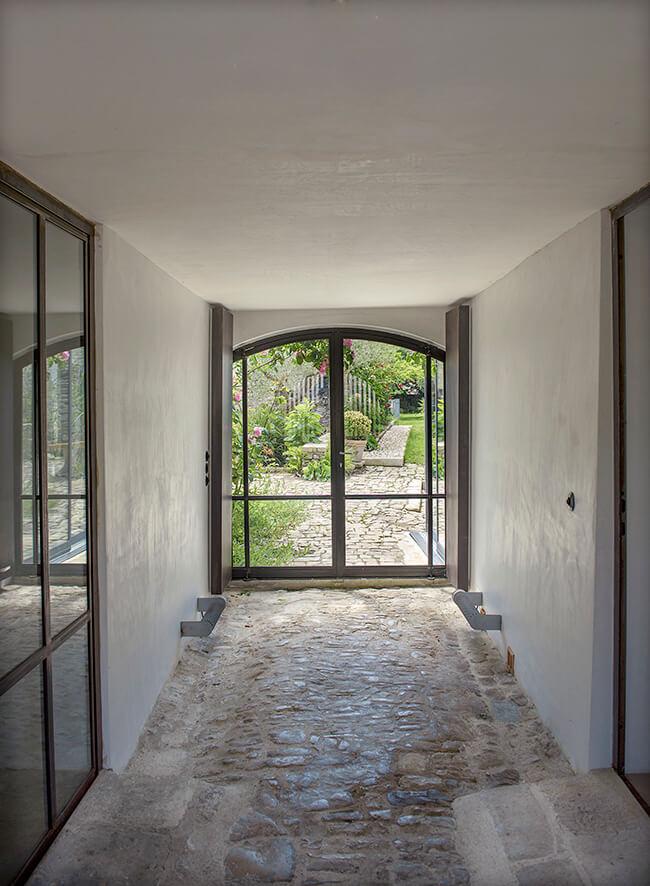 Couloir d'entrée avec pierre au sol et porte d'entrée en verre