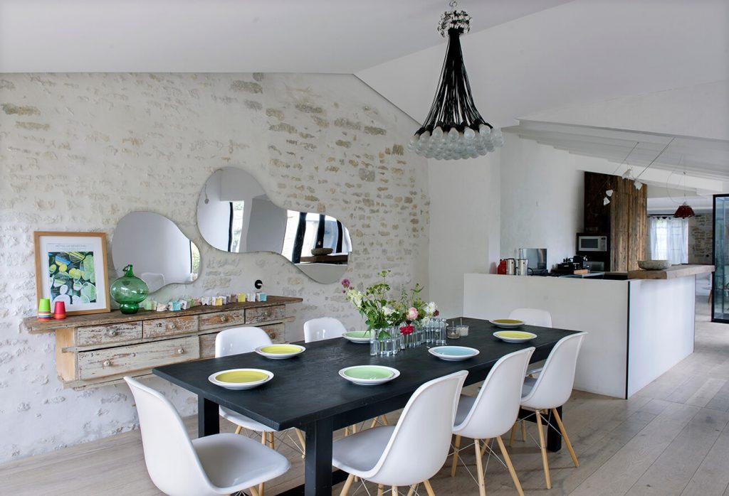 Cuisine ouverte avec une table noire et des chaises blanches