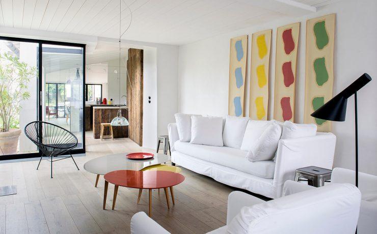 Salon maison contemporaine avec un canapé blanc et une table rouge