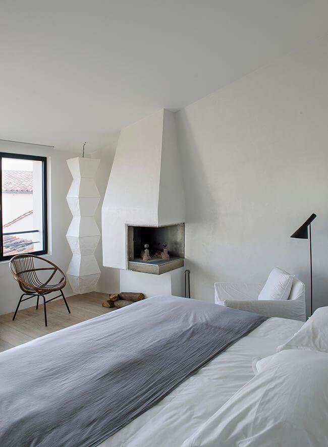 Petite cheminé dans une chambre avec un lit deux places