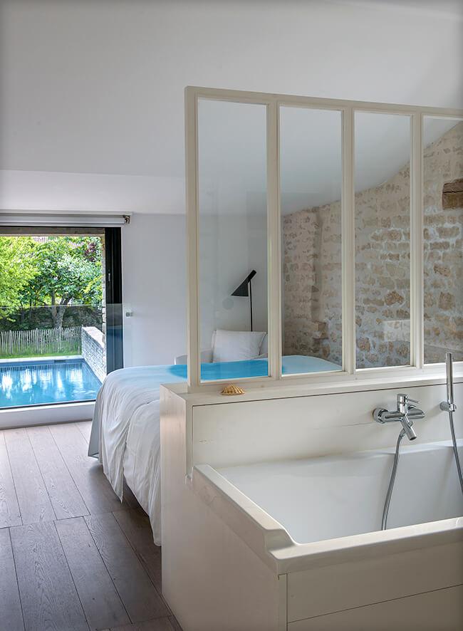 Verrière avec un lit et une grande baignoire blanche