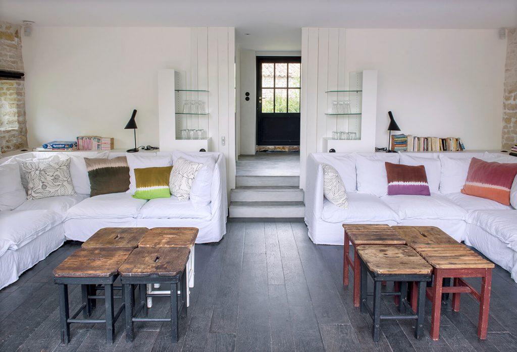 Salon avec grand canapé blanc et une table en bois au centre