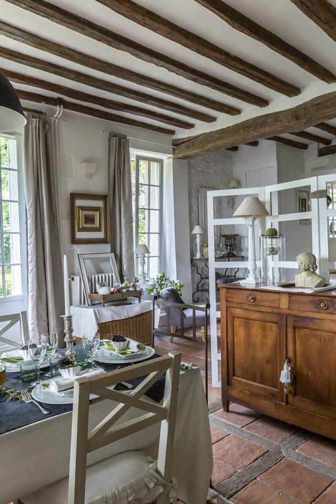 La salle à manger à la déco gustavienne avec une table, un meuble en bois et deux grandes fenêtres