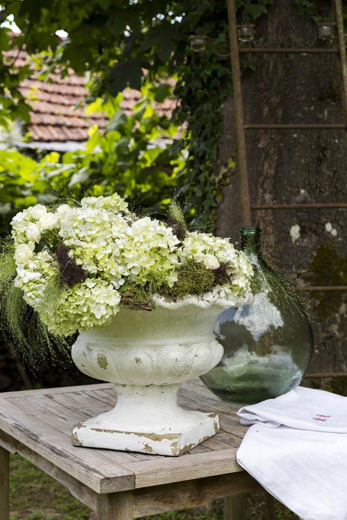 Des fleurs dans un pot de fleurs sur une table dans le jardin
