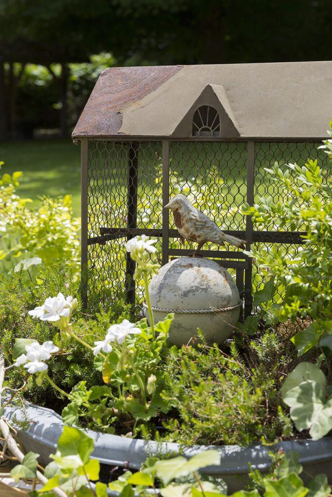 Une sculpture d'un oiseau sur une boule en pierre dans sa cage en ferraille