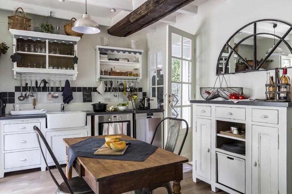 Cuisine à la déco gustavienne avec la table au milieu de la place et un miroir au dessus d'un meuble