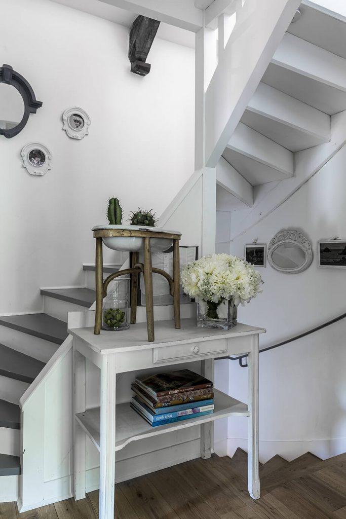 Des fleurs sur un meuble situé au milieu des escaliers dans une maison à la déco gustavienne