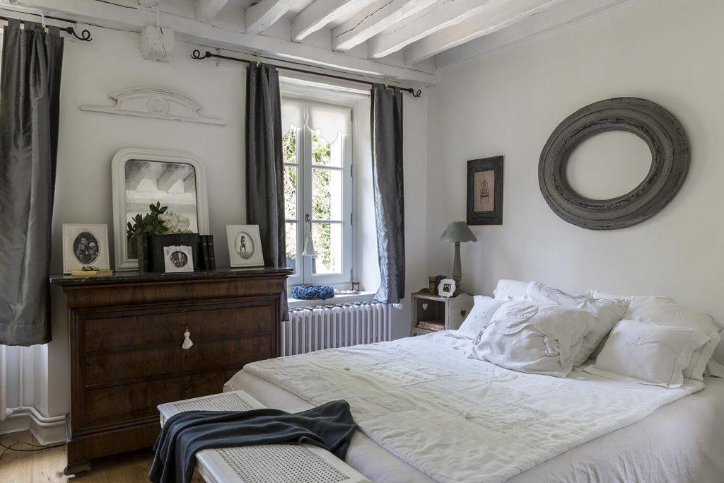 Chambre parentale composée d'un lit double, grandes fenêtres et meuble avec miroir à la déco gustavienne