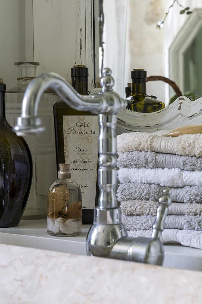 Robinet à l'ancienne dans une salle de bain et flacons anciens à la déco gustavienne
