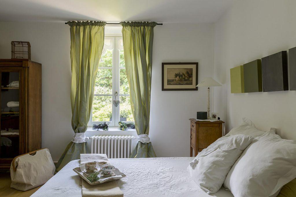 Chambre avec un lit double et une fenêtre avec rideaux verts à la déco gustavienne