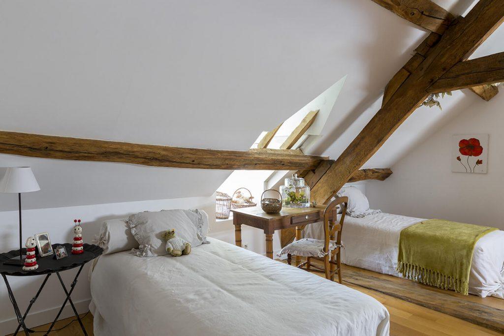 Chambre d'enfants avec deux lits simples et une peluche sur l'un de ces lits avec une déco gustavienne