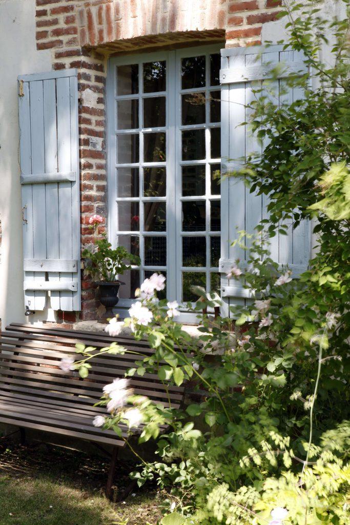 Dans le jardin, un banc en bois est situé sous une fenêtre