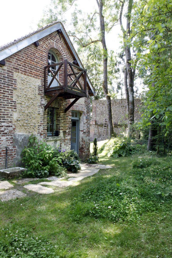 Un petit balcon en bois est situé à l'étage et il y a une fenêtre et une porte au rez-de-chaussée