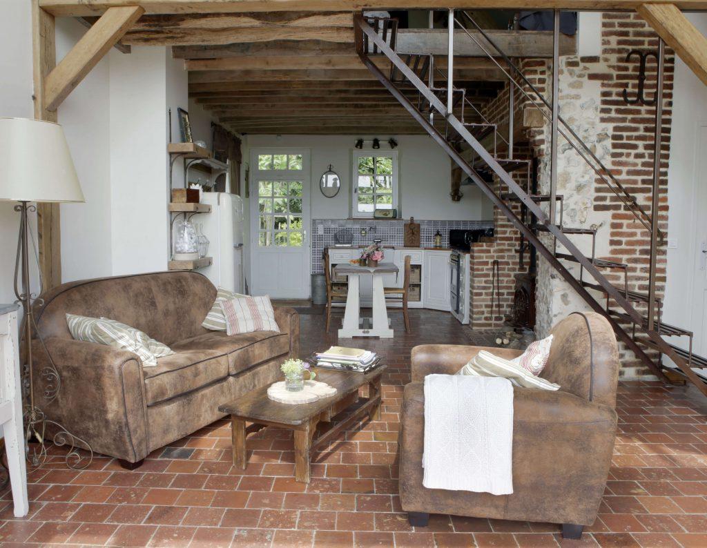 Un canapé et un fauteuil sont situés autour d'une table basse en bois pour une décoration rustique. A droite de la pièce, il y a les escaliers.