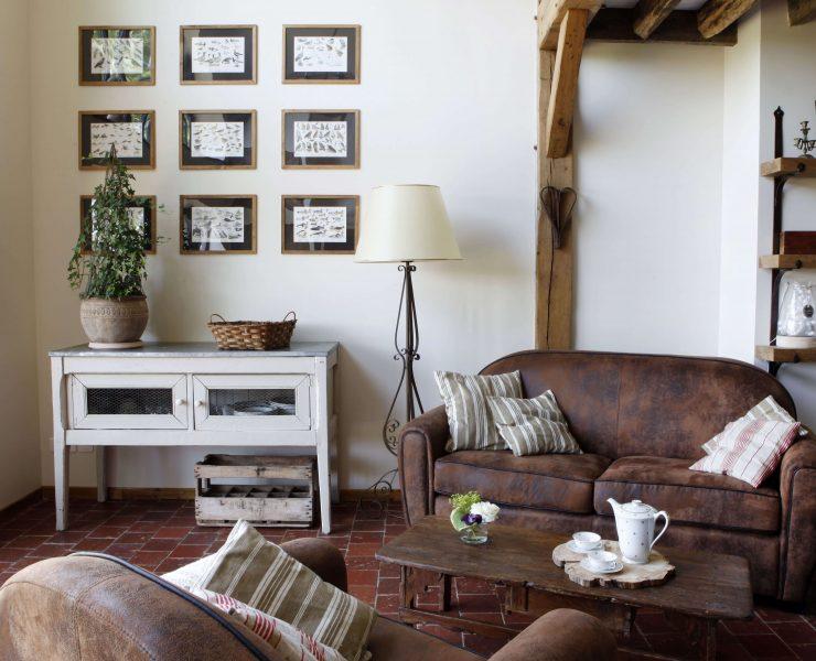 Dans le salon, derrière le canapé, il y a 9 cadres sur le mur représentant des familles d'oiseaux.