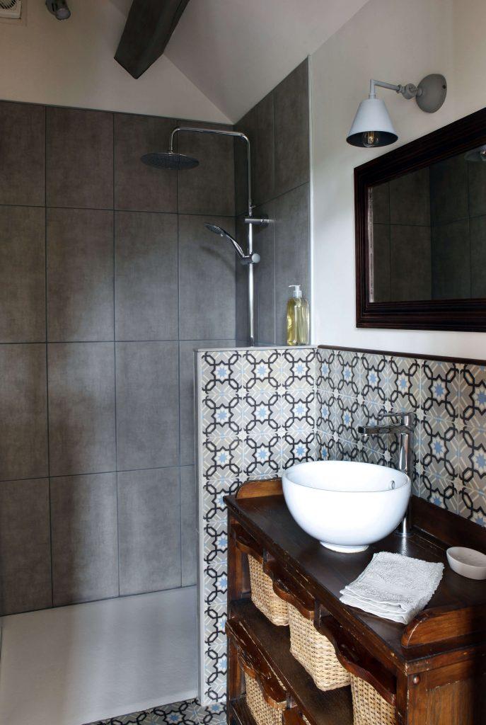 salle de bain avec douche au murs gris et lavabo arrondi