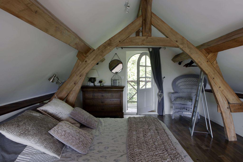 Dans la chambre à la décoration rustique chic, on retrouve le lit à gauche en face d'un miroir et d'une commode au fond de la pièce
