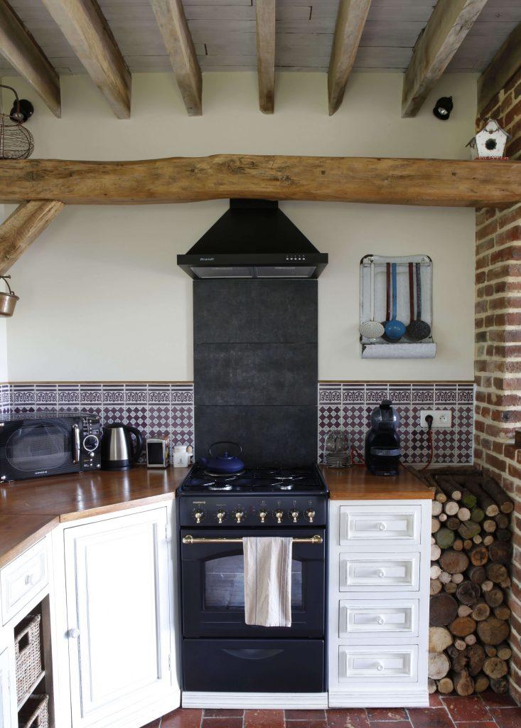 La gazinière noire se trouve au milieu d'un meuble blanc dans une cuisine à la décoration rustique. A côté de ce meuble, on retrouve le bois posé contre le mur.