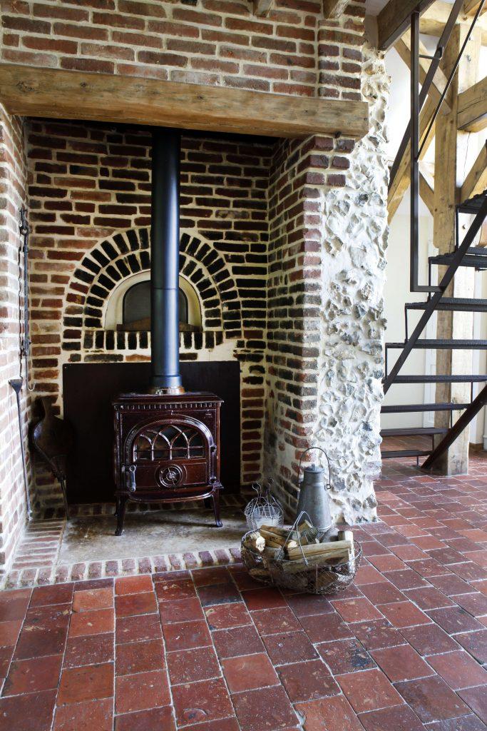Un poêle à bois rougeâtre est situé à côté des escaliers dans une cabane à la décoration rustique chic