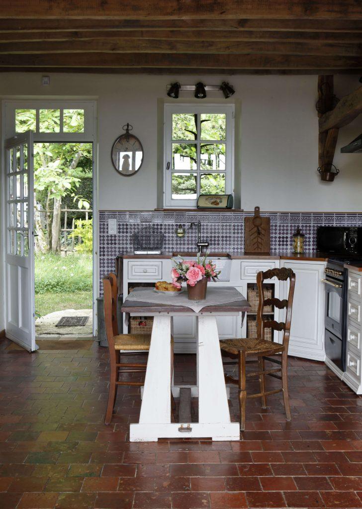 Dans la cuisine à la décoration rustique, il y a des fleurs sur la table au milieu de la pièce avec 4 chaises et une porte d'entrée au fond de la cuisine