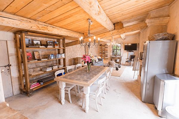Salle à manger d'une maison d'hôte avec table, frigo et bibliothèque