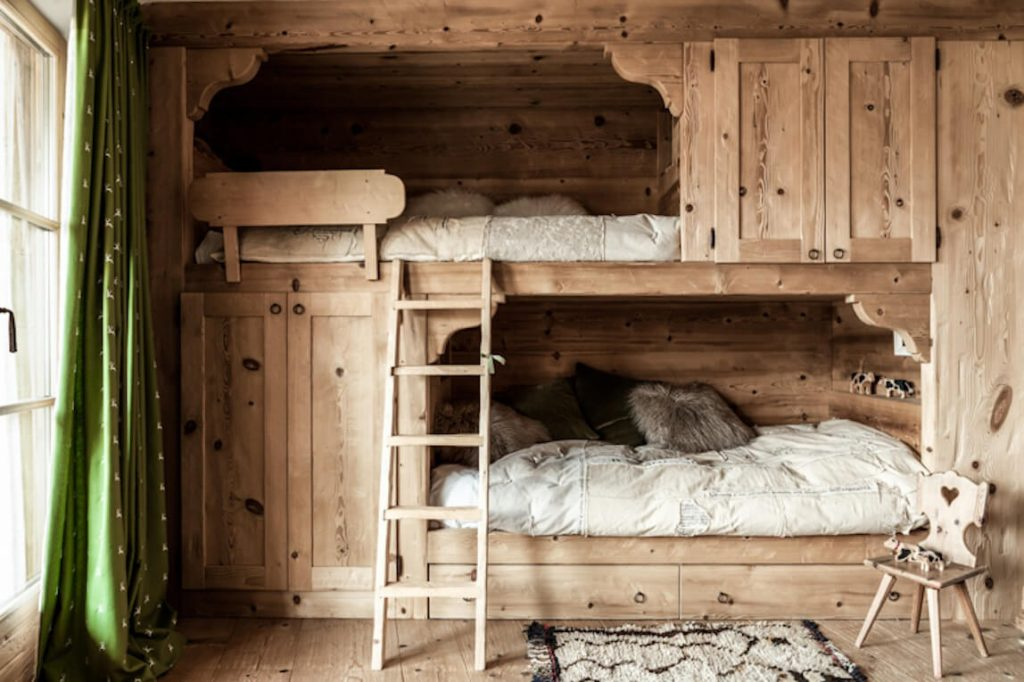 Chambre avec lit en bois dans un chalet en bois