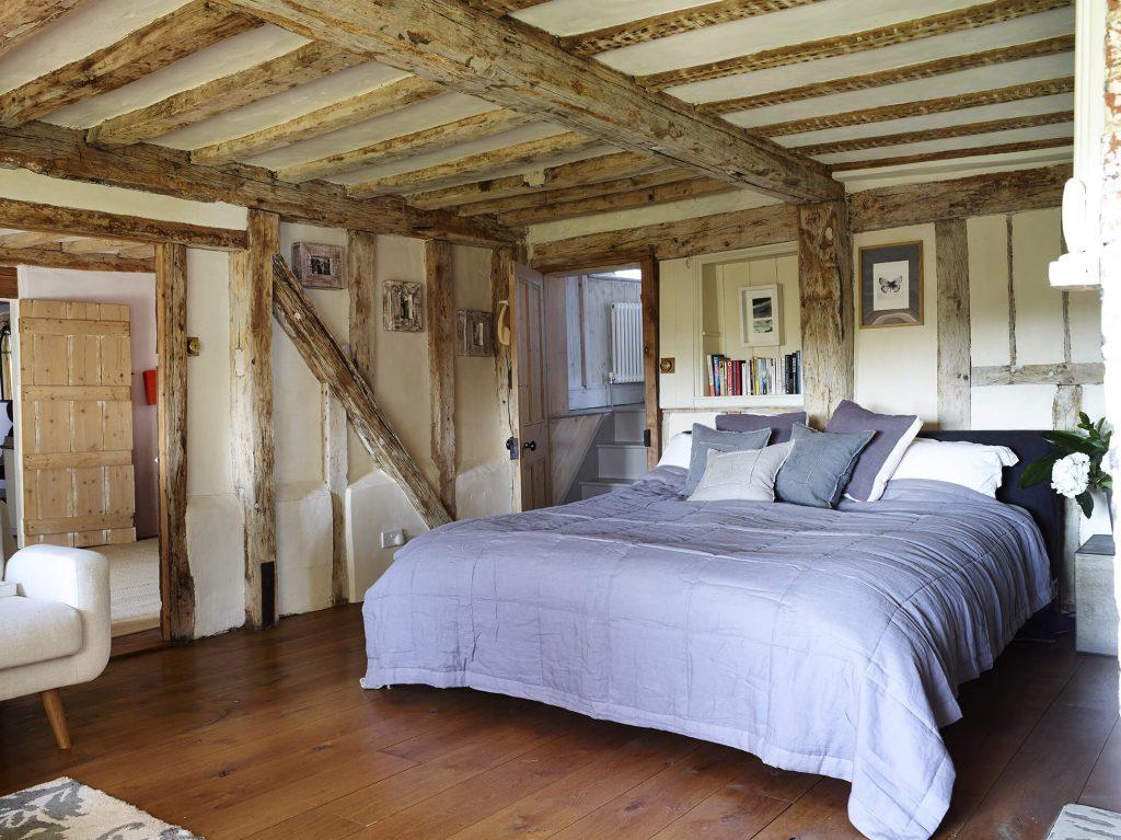 Lit avec drap mauve avec un plafond en poutre dans une maison de campagne au mélange de style