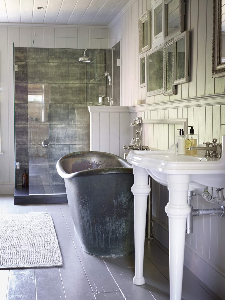 Baignoire noire avec lavabo blanc dans une salle de bain au mélange de style