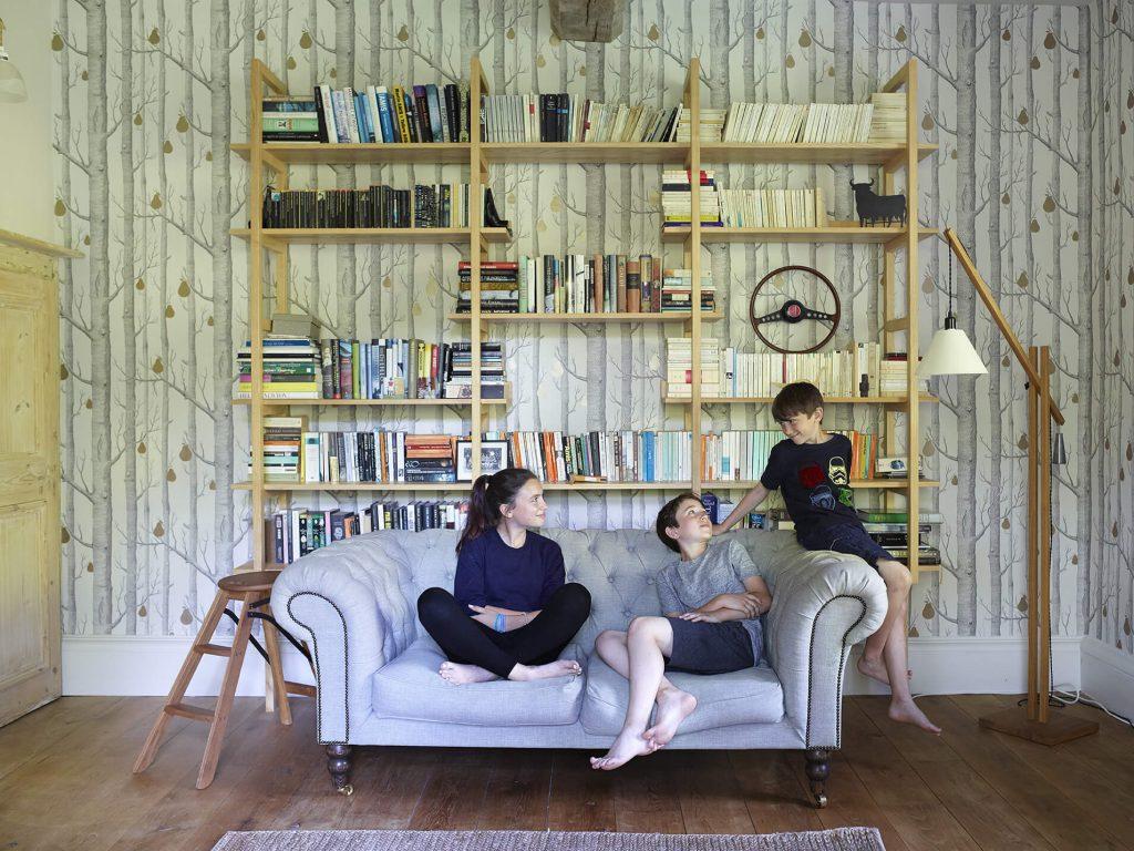 Bibliotheque avec un canapé et des enfants assis dessus dans une maison de campagne au mélange de style
