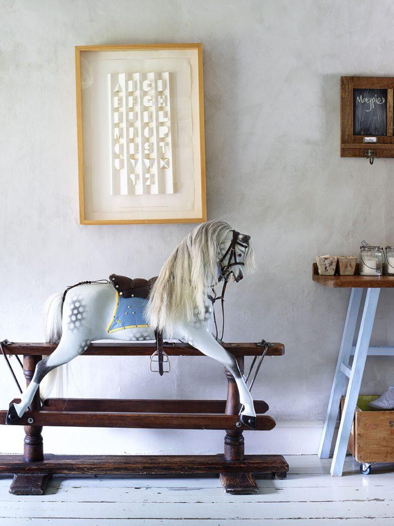 Cheval à bascule blanc dans une chambre d'enfant au mélange de style