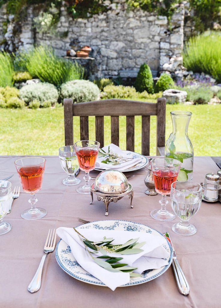 Assiette sur une table avec couverts dans le jardin d'une maison de campagne chic