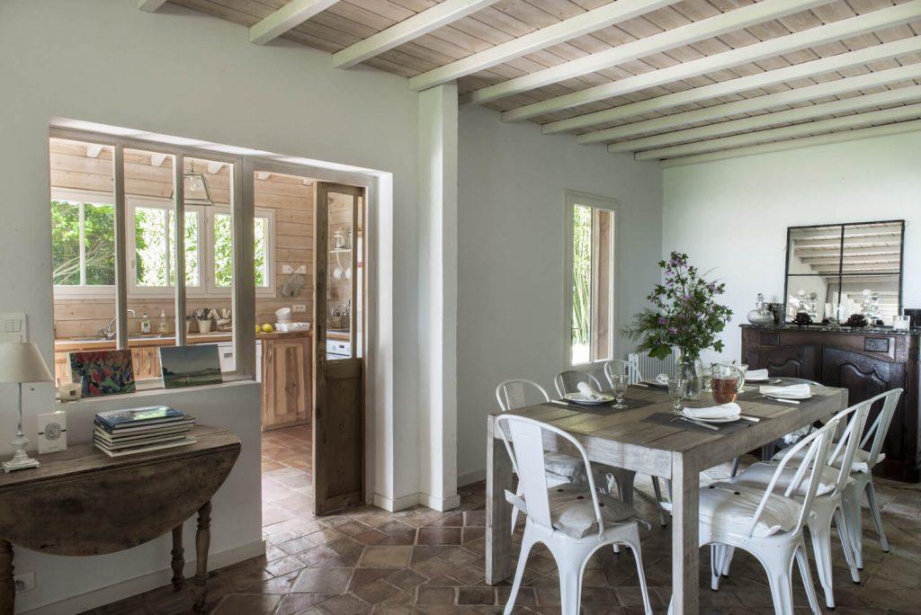 Verrière en bois avec une table à manger en bois et des chaises au style bord de mer