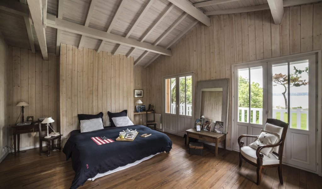 Lit deux place avec couverture noire dans une chambre en bois au style bord de mer