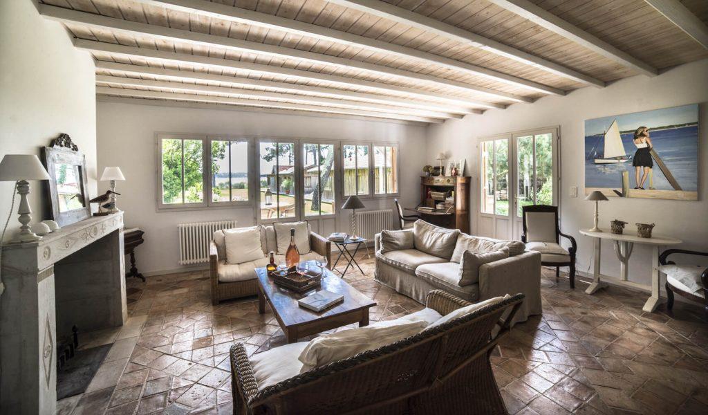 Salon avec trois canapés et une table noir au centre dans une cabane au style bord de mer
