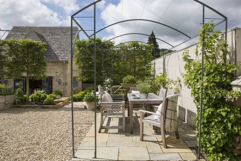 La terrasse du jardin avec une table, des chaises et des plantes vertes