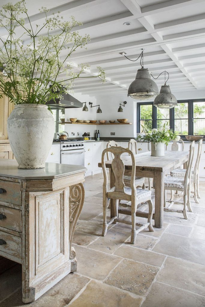 La cuisine avec la table, les chaises et une plante verte sur un comptoire