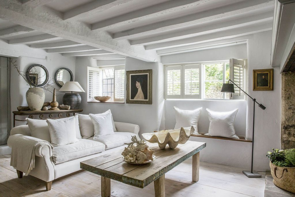 C'est le salon avec une table en bois au mileu et deux canapés blancs autour de cette table, il y a également une cheminée