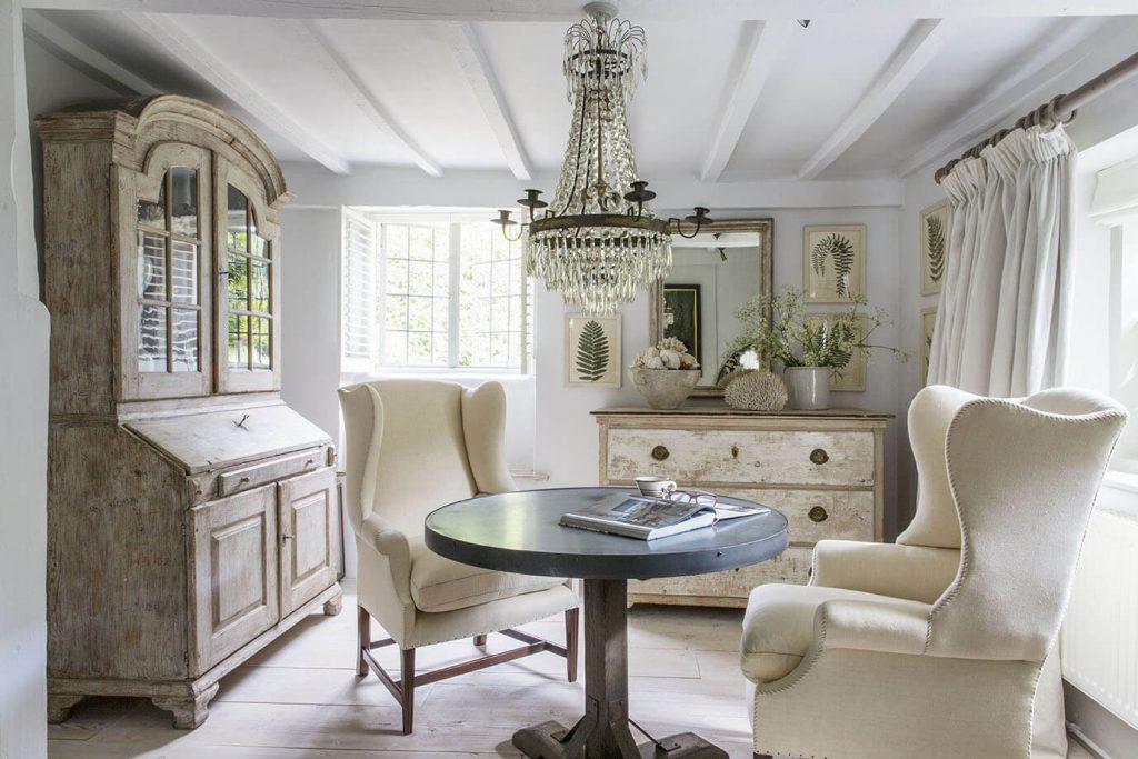 C'est le salon de lecture avec une commode, une table ronde et deux fauteuils blancs